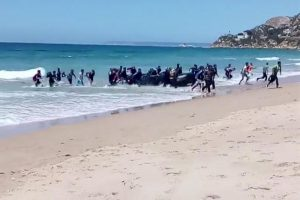 In this image taken from video, migrants scatter as a rubber dingy lands on the beach at Cadiz, southern Spain, Wednesday Aug. 9, 2017. Beachgoers watched as around two dozen suspected migrants scattering on the beach. Disembarkations by migrants on Spanish beaches aren't common but have happened before, especially at Spain's north African enclave cities of Melilla and Ceuta, which border Morocco. (Carlos Sanz via AP)